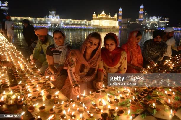 TOPSHOT Indian Sikh devotees light lights diyas during Bandi Chhor Divas or Diwali at the Golden Temple in Amritsar on November 7 2018 Sikhs...