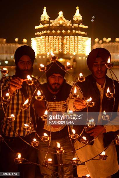 Indian Sikh devotees light oil lamps at the Golden Temple in Amritsar on November 13 on the ocassion of Bandi Chhor Divas or Diwali Sikhs celebrate...