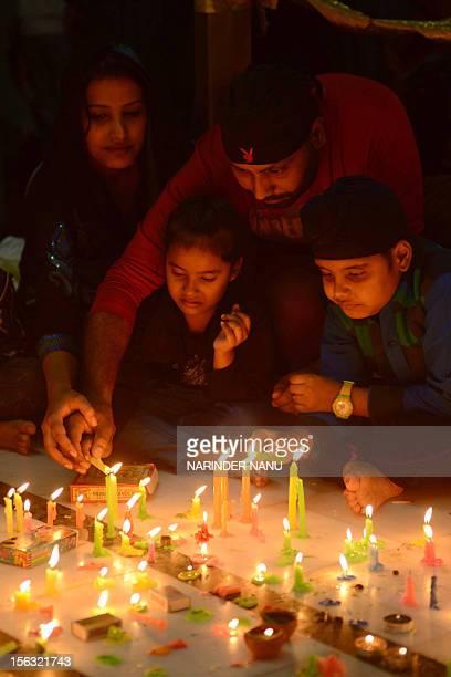 Indian Sikh devotees light oil lamps at the Golden Temple in Amritsar on November 13 on the ocassion of Bandi Chhor Divas or Diwali Sikhs celebrate...