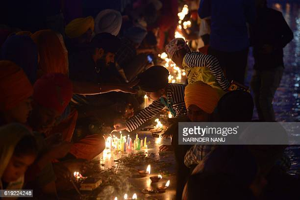Indian Sikh devotees lighting candles during Bandi Chhor Divas or Diwali at the Golden Temple in Amritsar on October 30 2016 Sikhs celebrate Bandi...