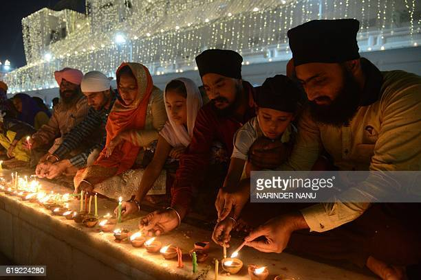 Indian Sikh devotees lighting candles during Bandi Chhor Divas or Diwali at the Golden Temple in Amritsar on October 30 2016 Sikhs celebrate Bandi...