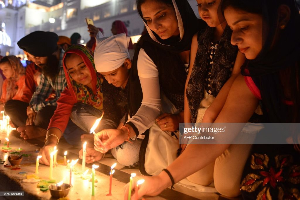Indian Sikh devotees lighting candles on the occasion of th 548th birth anniversary of Sri Guru Nanak Dev at the Golden Temple in Amritsar on...