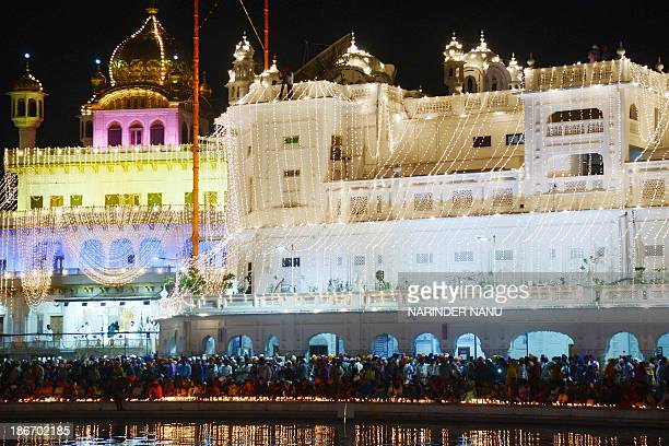 Indian Sikh devotees lights candles at the illuminated Sikhism's holiest shrine Golden Temple in Amritsar on November 3 on the ocassion of Bandi...