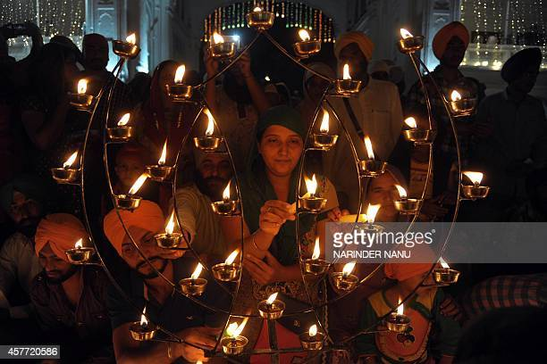 Indian Sikh devotees ligting candles on the occasion of Bandi Chhor Divas or Diwali at the illuminated Golden Temple in Amritsar India on October 23...