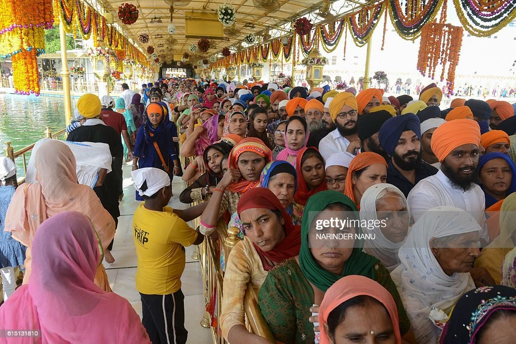 Indian Sikh devotees line up to pay respects as a `Jalau` ritual takes place inside the Sikh Shrine Golden Temple in Amritsar on October 17 2016 The..