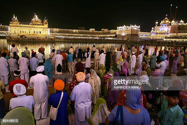 Indian Sikh devotees offer prayers in front of the illuminated Golden Temple on the eve of the festival of Bandi Chhor Divas in Amritsar on October...