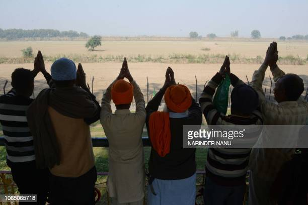 Indian Sikh devotees offers prayers as they look towards the Gurdwara Kartarpur Sahib which is situated in Pakistan from Indian side at Dera Baba...