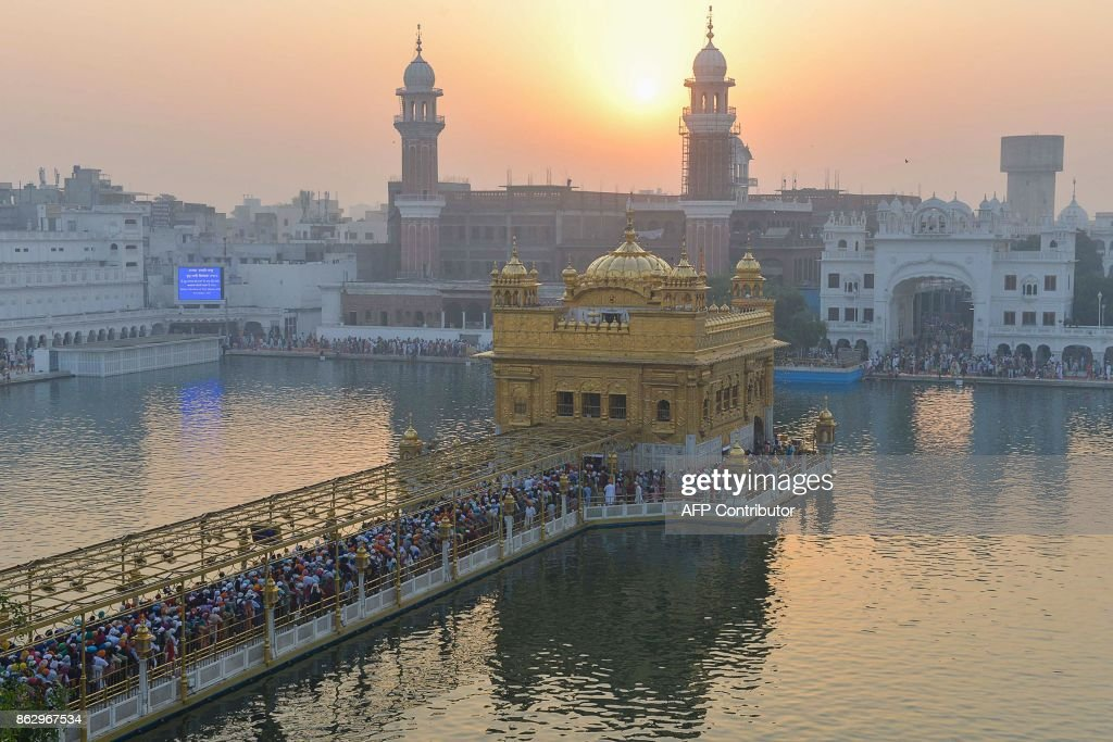 Indian Sikh devotees pay respect in the early morning during Diwali Festival at the illuminated Golden Temple in Amritsar on October 19 2017 Diwali...