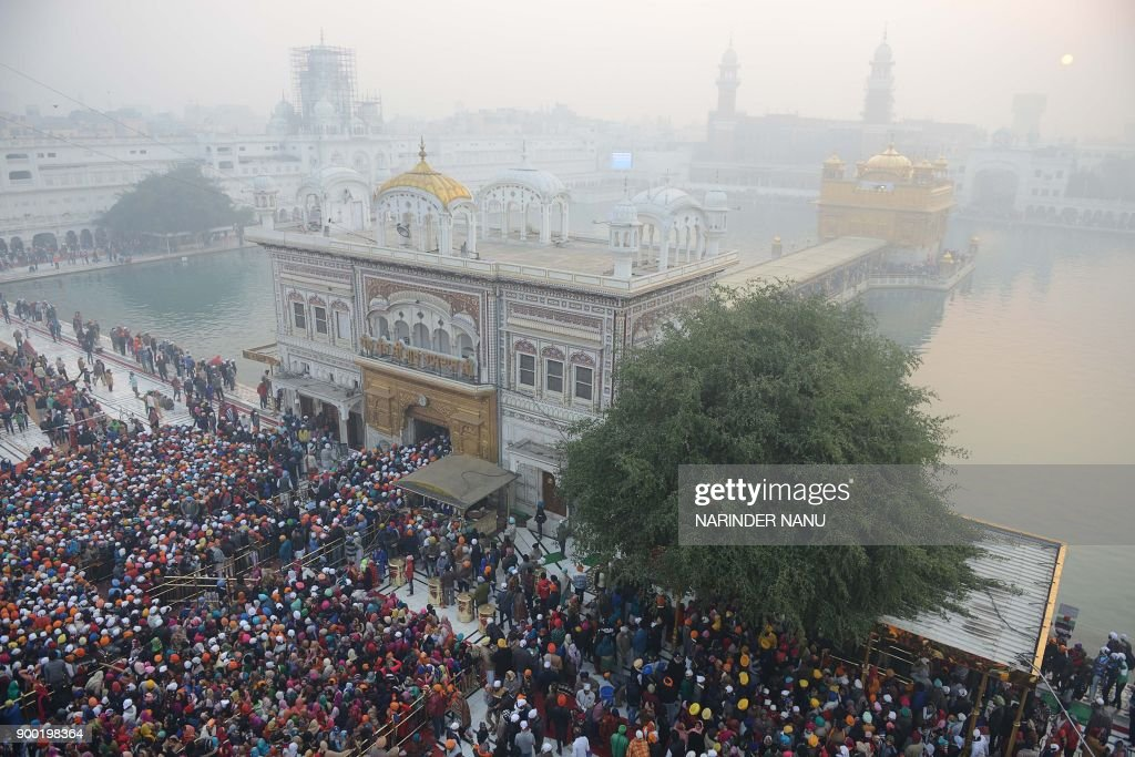 Indian Sikh devotees pay respect on the occasion of the New Year 2018 at the Golden Temple in Amritsar on January 1 2018 / AFP PHOTO / NARINDER NANU