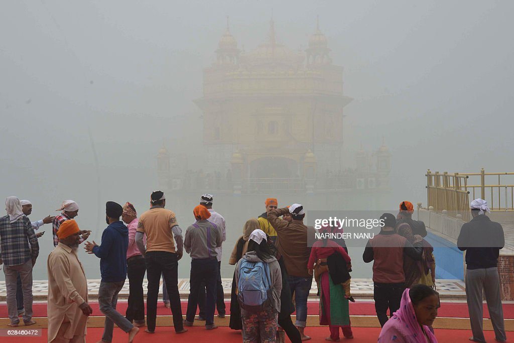 Indian Sikh devotees pay respects during dense fog at the Golden Temple in Amritsar on December 8 2016 / AFP / Narinder NANU