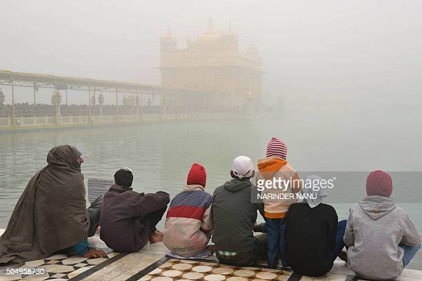 Indian Sikh devotees pay respects on the occasion of Maghi Mela during dense fog at the Golden Temple in Amritsar on January 14 2016 Maghi Mela...