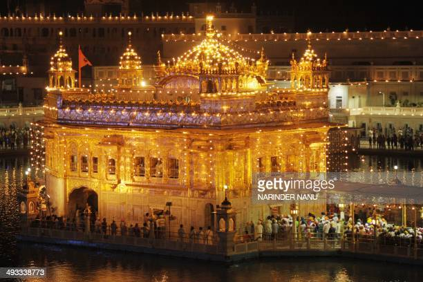 Indian Sikh devotees pay their respects at the Golden Temple in Amritsar on May 23 2014 Sikh devotees are marking the 535th birth anniversary of Guru...