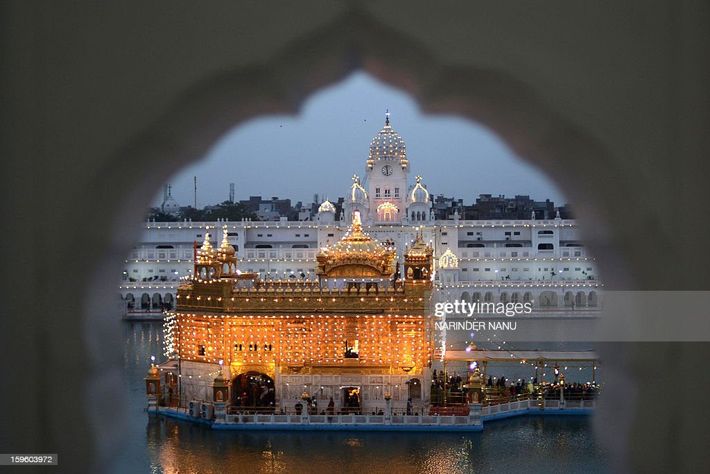 Indian Sikh devotees pay their respects at the illuminated Golden Temple in Amritsar on January 17, 2013, on the eve of the 348th Birth Anniversary of tenth Sikh Guru Gobind Singh.