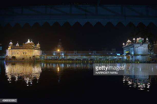 Indian Sikh devotees pay their respects at the illuminated Sikh shrine Golden temple in Amritsar on November 112015 on the occasion of Bandi Chhor...