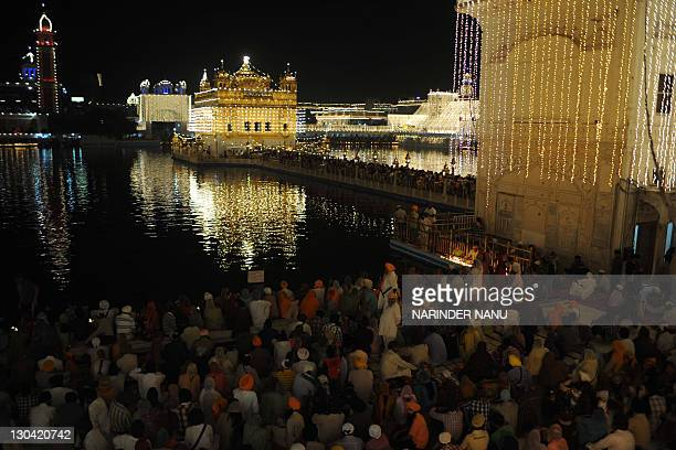 Indian Sikh devotees pay their respects at the illuminated Sikh Shrine The Golden Temple in Amritsar on October 26 on the occasion of Bandi Chhor...
