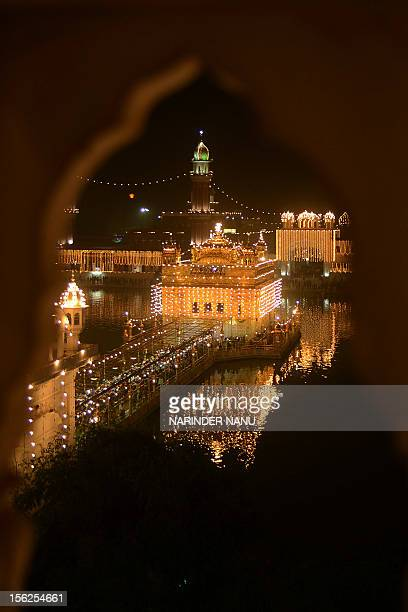 Indian Sikh devotees pay their respects at the illuminated Sikhism's holiest shrine Golden Temple in Amritsar on November 12 on the eve of Bandi...