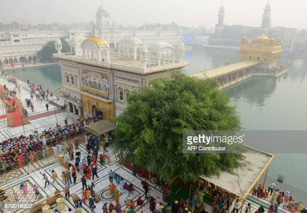 Indian Sikh devotees pay their respects during an event to mark 548th birth anniversary of Sri Guru Nanak Dev at the Golden Temple in Amritsar on...