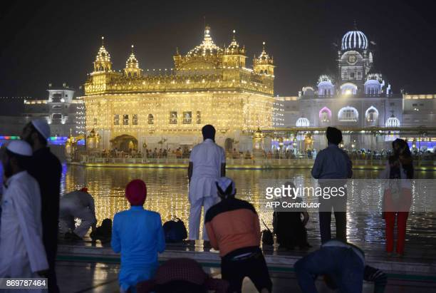 Indian Sikh devotees pay their respects on the eve of 548th birth anniversary of Sri Guru Nanak Dev at the Golden Temple in Amritsar on November 3...
