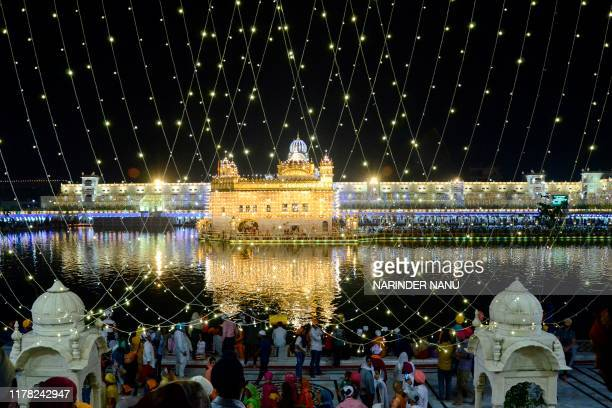 TOPSHOT Indian Sikh devotees pay their respects on the eve of Bandi Chhor Divas or Diwali at the illuminatedGolden Temple in Amritsar on October 26...