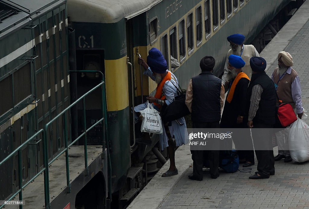 Indian Sikh devotees reboard a train at Wagah railway station after clearing immigration at Wagah on November 12 as they arrive in Pakistan from...
