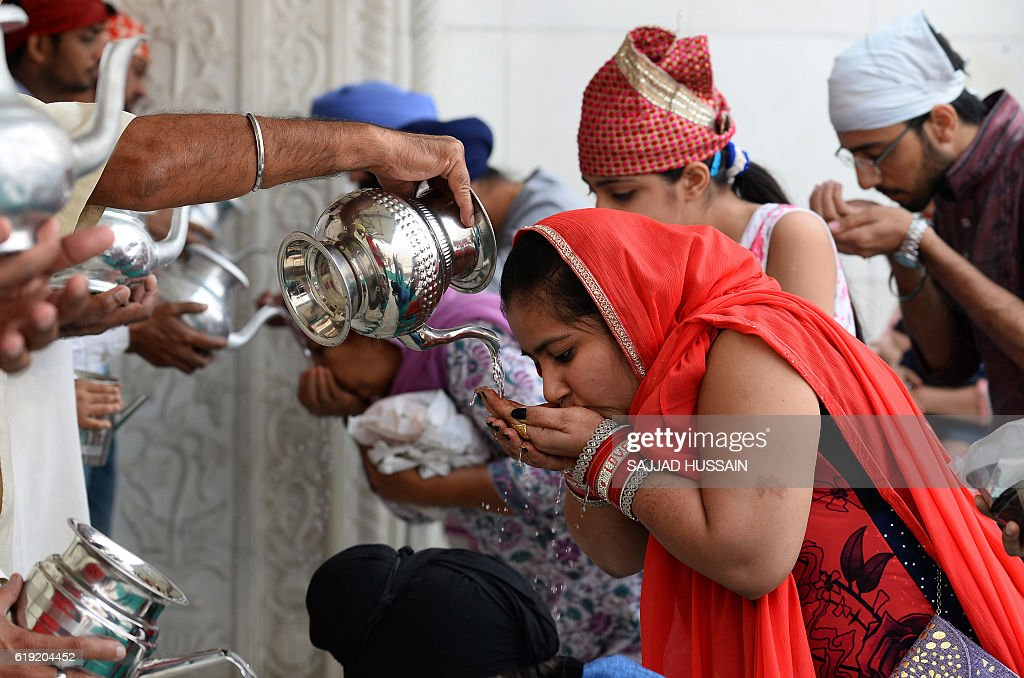 Indian Sikh devotees receive holy water on the occasion of Bandi Chhor Divas, or Diwali, at a Sikh temple (Gurdwara) in New Delhi on October 30, 2016. Sikhs celebrate Bandi Chhor Divas, or Diwali, to mark the return of the sixth Guru, Guru Hargobind Ji, who was freed from imprisonment and also managed to release 52 political prisoners at the same time from Gwalior fort held by Mughal Emperor Jahangir in 1619. / AFP / SAJJAD