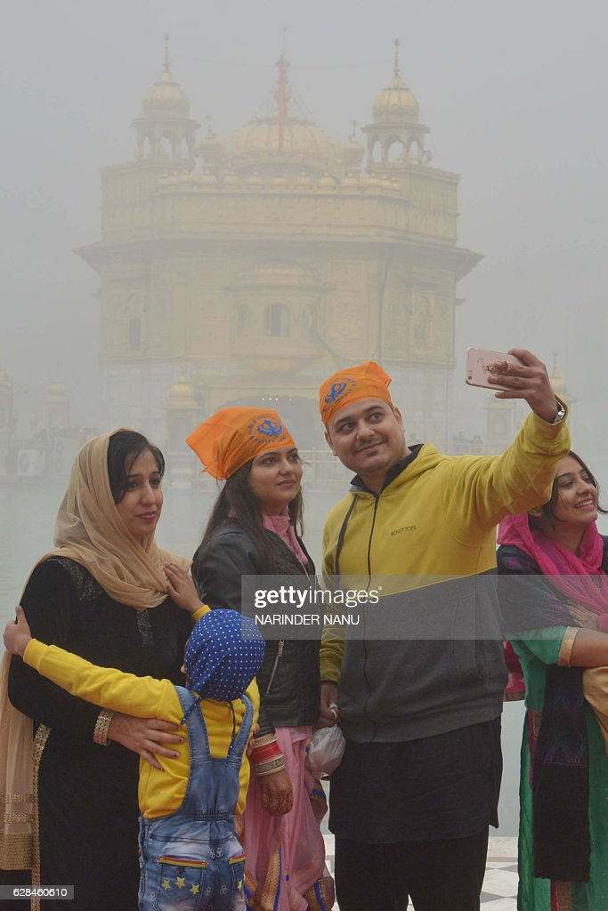 Indian Sikh devotees take a selfie photograph during dense fog at the Golden Temple in Amritsar on December 8 2016 / AFP / NARINDER NANU