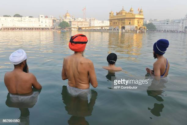 Indian Sikh devotees take an early morning dip in the holy water tank 'sarovar' during Diwali Festival at the illuminated Golden Temple in Amritsar...
