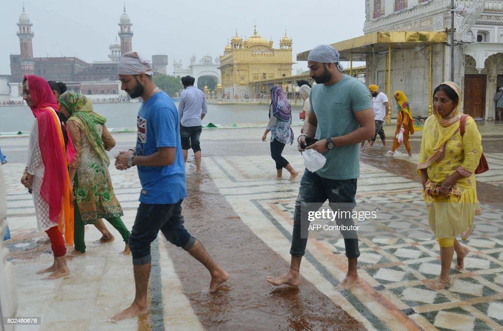 Indian Sikh devotees walk through rain water amid showers at the Golden Temple in Amritsar on June 28 2017 / AFP PHOTO / NARINDER NANU
