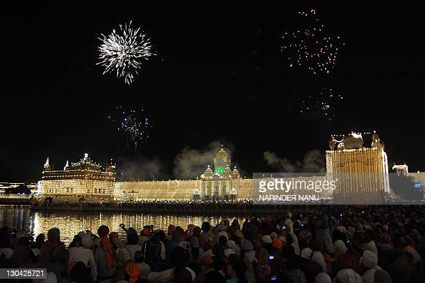 Indian Sikh devotees watch a fireworks display above Sikhism's holiest shrine The Golden Temple in Amritsar on October 26 on the occasion of Bandi...