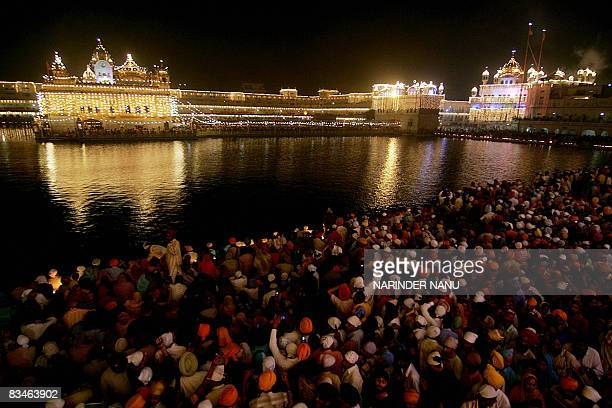 Indian Sikh devotees watch a fireworks display over the illuminated Golden Temple in Amritsar on October 28 2008 on the occasion of the festival of...