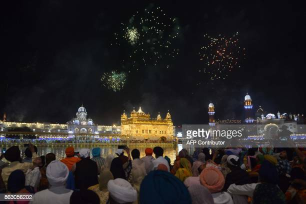 Indian Sikh devotees watch fireworks as they mark Bandi Chhor Divas or Diwali at the Golden Temple in Amritsar on October 19 2017 Sikhs celebrate...