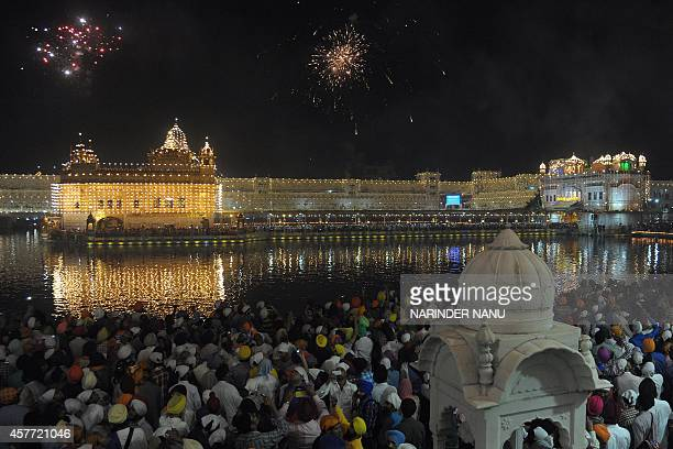 Indian Sikh devotees watch fireworks on the occasion of Bandi Chhor Divas or Diwali at the illuminated Golden Temple in Amritsar India on October 23...