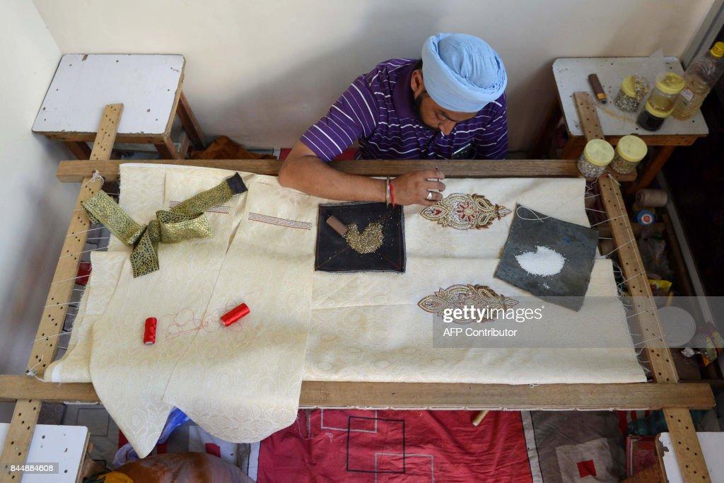 Indian Sikh Gurdev Singh embroider works on a wedding dress for groom at a studio boutique in Amritsar on September 9 2017 / AFP PHOTO / NARINDER NANU