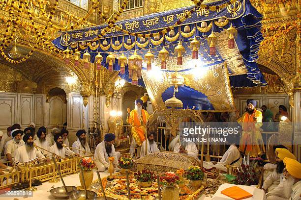 Indian Sikh head Priest Jaswinder Singh sits behind the Guru Granth Sahib Sikh Holy Book during a ceremony inside The Golden Temple in Amritsar on...