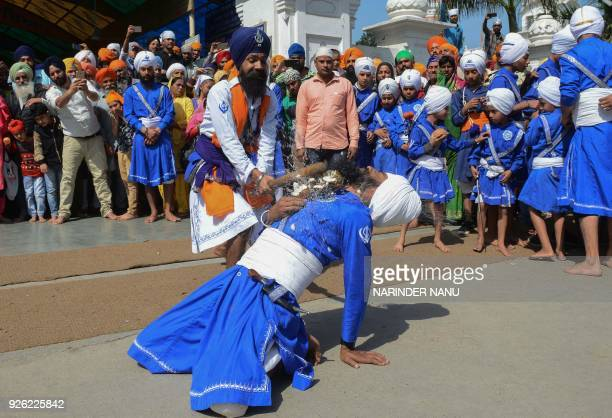 Indian Sikh men performs 'Gatka' an ancient form of Sikh martial art during a procession to mark 'Hola Mohalla' at the Golden Temple in Amritsar on...