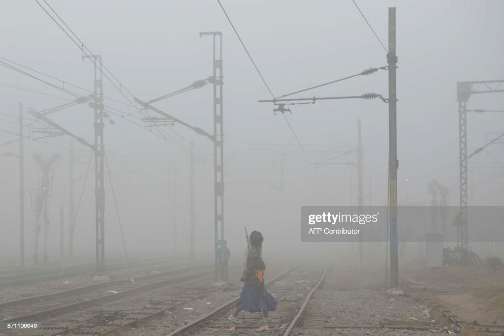 Indian Sikh `Nihang` or traditional Sikh army member crosses railway tracks amidst dense smog near Amritsar railway station on November 7 2017...
