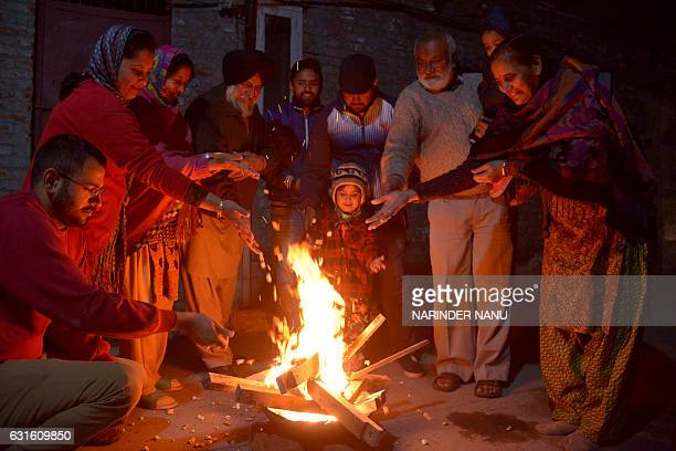 Indian Sikh people toss puffed rice, peanuts and popcorn into a bonfire during celebrations on the occasion of the Lohri festival in Amritsar on...