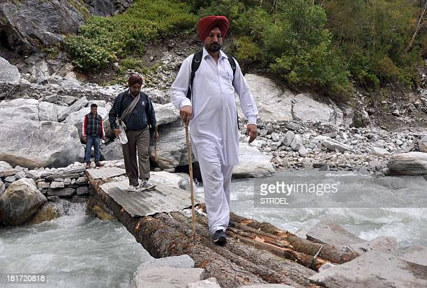 Indian Sikh pilgrims journey along a bridge in The Valley of Flowers in Chamoli District on September 22 as devotees were allowed to resume...