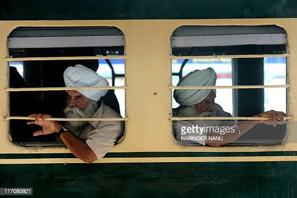 Indian Sikh pilgrims look out of a window after boarding a train for Pakistan at a railway station in Amritsar on June 21 2011 Hundreds of Indian...