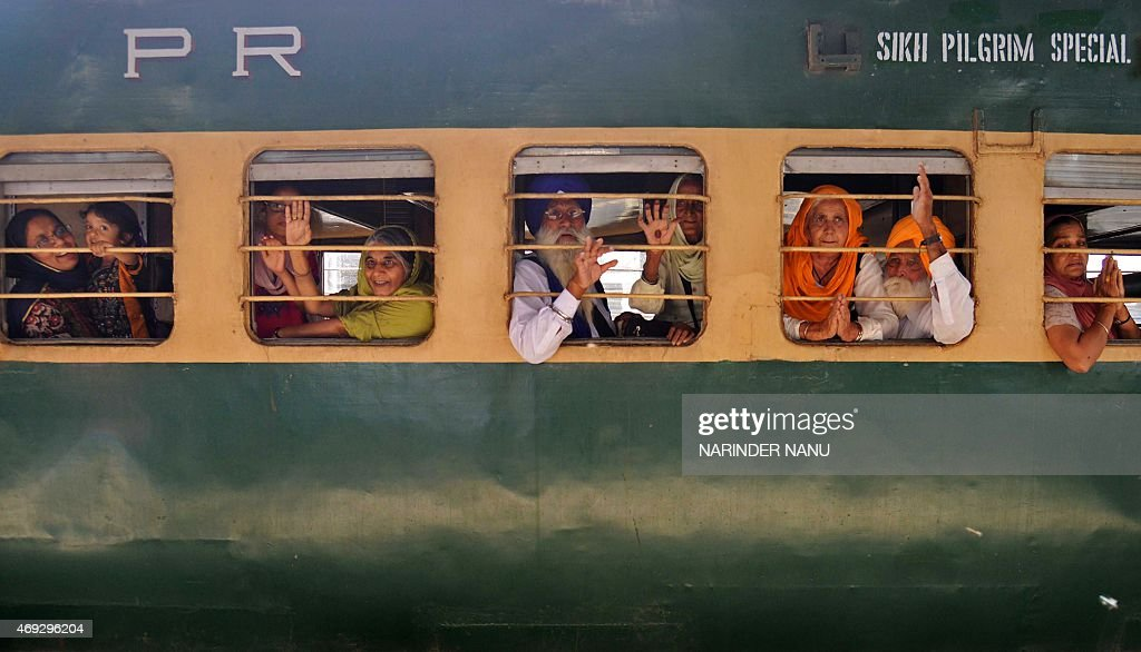 Indian Sikh pilgrims pose for a photograph after boarding a train for Pakistan at a railway station in Amritsar on April 11 2015 Thousands of Indian..