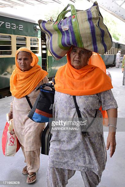 Indian Sikh pilgrims returning from Pakistan arrive at the Attari railway station some 35 kms from Amritsar on June 30 2013 Hundreds of Indian Sikh...