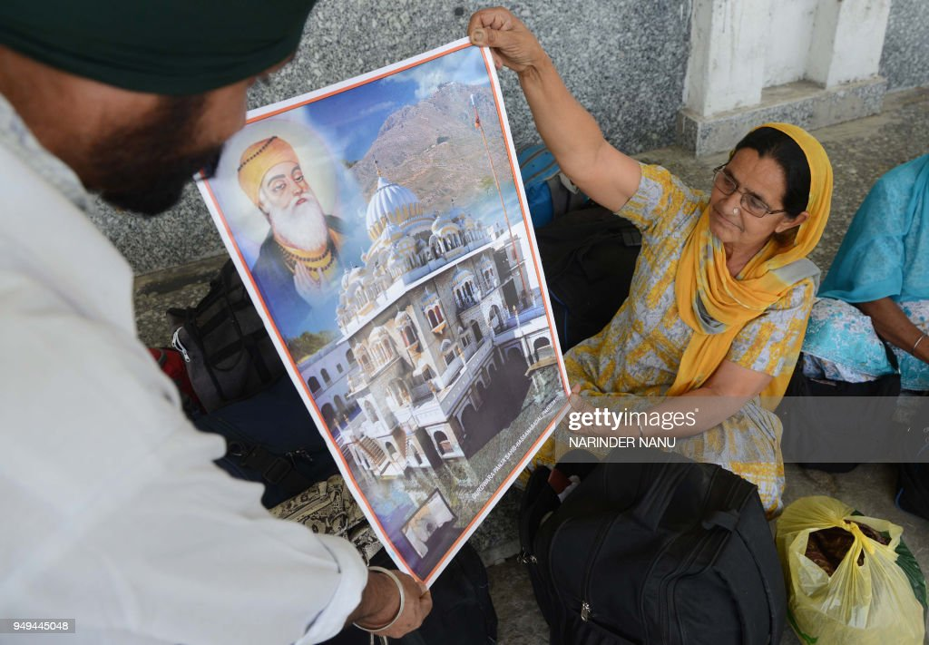 Indian Sikh pilgrims returning from Pakistan unfurl a poster of the Gurdwara Panja Sahib in Pakistan after they arrive at Attari railway station some.