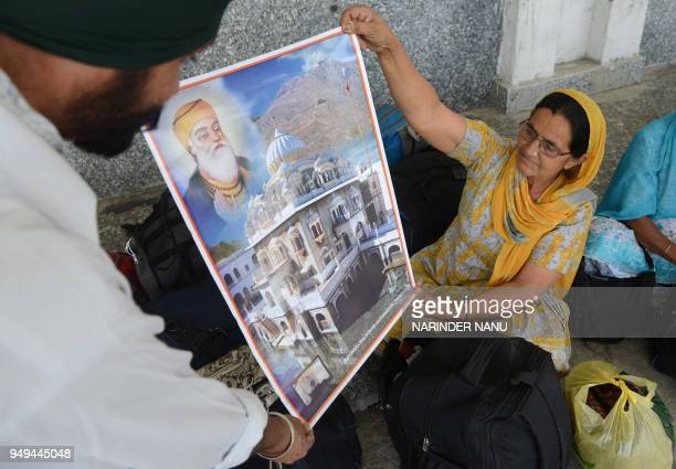 Indian Sikh pilgrims returning from Pakistan unfurl a poster of the Gurdwara Panja Sahib in Pakistan after they arrive at Attari railway station some...