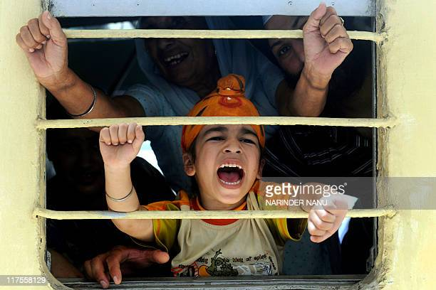 Indian Sikh pilgrims shout slogans after boarding a train for Pakistan at a railway station in Amritsar on June 21 2011 Hundreds of Indian Sikh...