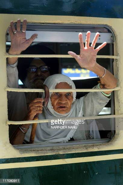 Indian Sikh pilgrims wave after boarding a train for Pakistan at a railway station in Amritsar on June 21 2011 Hundreds of Indian Sikh pilgrims are...