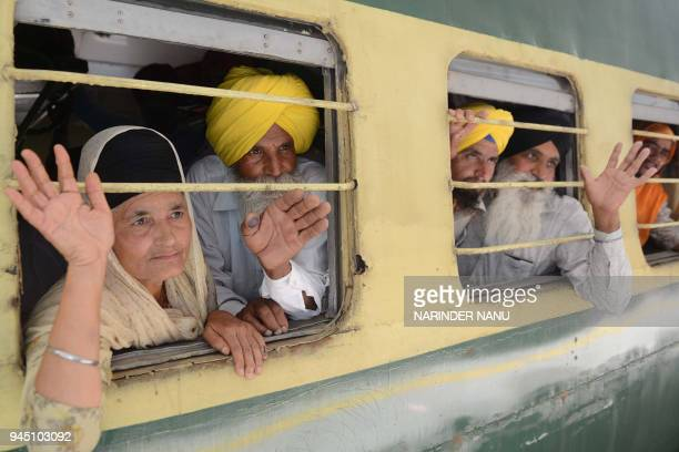 Indian Sikh pilgrims wave from their train at Attari Railway Station before leaving on special service to Lahore to celebrate the Baisakhi festival...