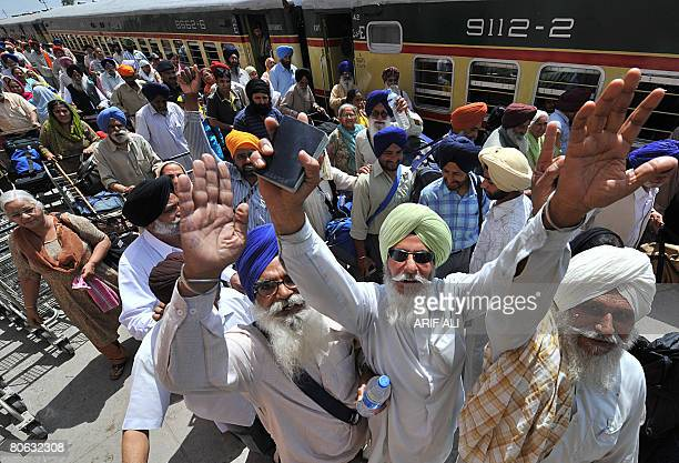 Indian Sikh pilgrims wave upon arrival at Wagah Railway Station in Wagah on April 11 2008 The first batch of Sikh pilgrims arrived in Pakistan from...