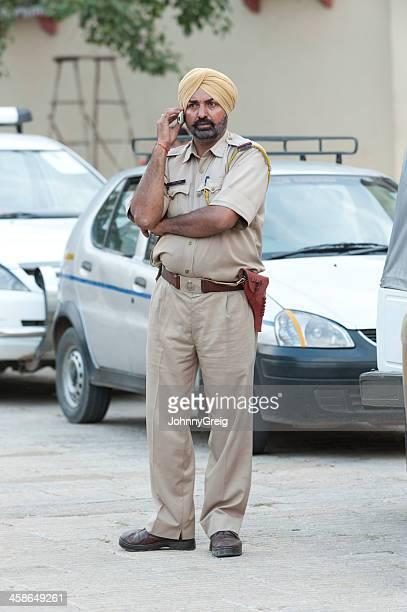 Indian Sikh policeman talking on mobile phone
