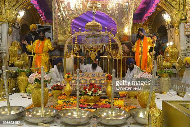 Indian Sikh priest Balwinder Singh sits behind the Sikh Holy BookThe Guru Granth Sahib during a 'Jalau' a splendour show of Sikhism's symbolic items...