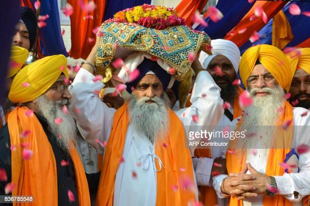 Indian Sikh priest Giani Jagtar Singh carries the Guru Granth Sahib the central religious text of Sikhism during a religious procession to mark the...